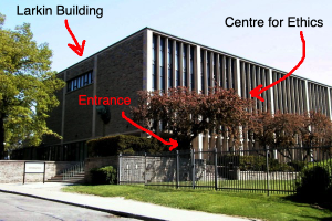 Photo of Larkin Building with arrows pointing to the entrance and the Centre for Ethics, located on the second floor.